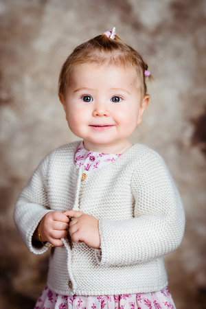 Portrait of sweet blond little girl with big grey eyes and plump cheeks keeping her finger in her hand. Studio portrait brown grunge background