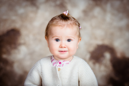 Surprised blond little girl with big grey eyes and plump cheeks. Studio portrait on brown grunge background