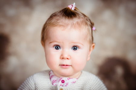 Amazed little girl with big grey eyes and plump cheeks. Close-up studio portrait on brown grunge background