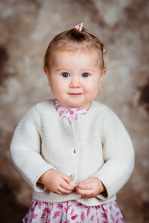 Portrait of beautiful blond little girl with big grey eyes and plump cheeks looking at camera. Studio portrait on brown grunge background photo
