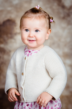 Portrait of beautiful smiling blond little girl with big grey eyes and plump cheeks. Studio portrait on brown grunge background Фото со стока