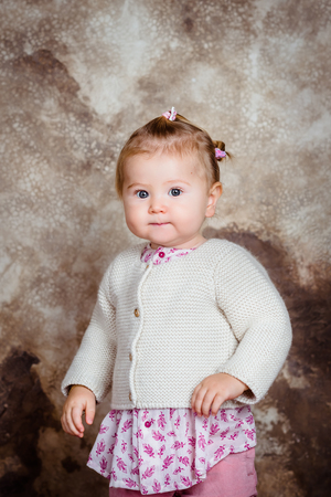 Serious little girl with blond hair and plump cheeks looking at camera. Studio portrait on brown grunge background Фото со стока