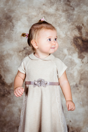 hilarity: Beautiful little girl with blond hair and plump cheeks wearing stylish beige dress