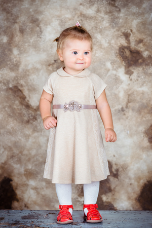 Adorable little girl with blond hair and plump cheeks wearing stylish beige dress and red shoes Фото со стока