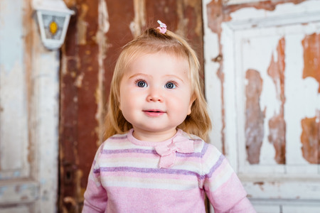 grey eyed: Surprised funny blond little girl with big grey eyes and plump cheeks looks up. Studio portrait on grunge wooden background Stock Photo
