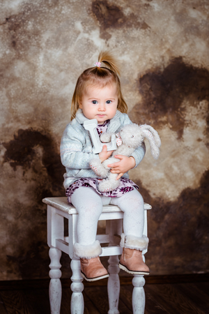 Cute blond little girl sitting on white chair and holding her toys. Studio portrait on brown grunge background Фото со стока