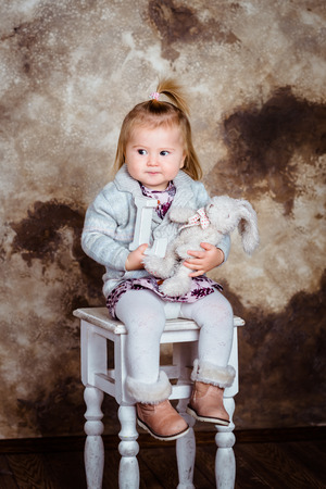 chubby girl: Displeased blond little girl sitting on white chair and holding her toys. Studio portrait on brown grunge background