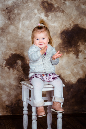 Adorable little girl with blond hair sitting on chair, laughing and clapping her hands. Studio portrait on brown grunge background Фото со стока