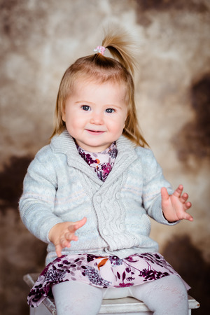 Sweet smiling little girl with blond hair sitting on chair and clapping her hands. Studio portrait on brown grunge background