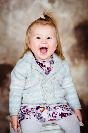 Cute little girl with blond hair sitting on white chair and laughing