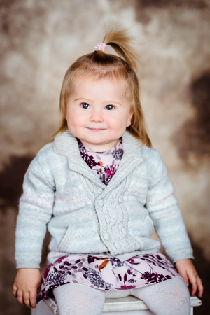 Adorable little girl with blond hair sitting on white chair and smiling Фото со стока