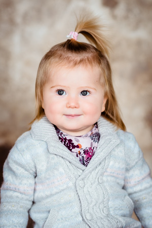 Close-up studio portrait of sweet little girl with blond hair and plump cheeks Фото со стока