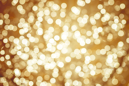 golden light: Golden background with natural bokeh defocused sparkling lights. Colorful metallic texture with twinkling lights. Bright and vivid colors