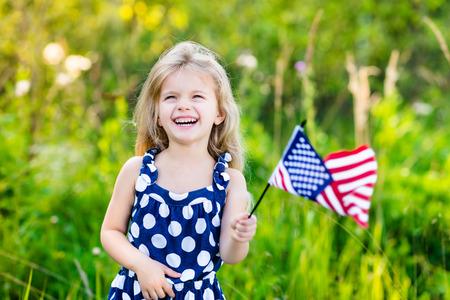 independencia: Niña bonita con el pelo largo y rubio y rizado que sostiene una bandera americana, agitándolo y riendo en día soleado en el parque de verano. Día de la Independencia, el concepto de Día de la Bandera