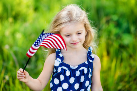 Pretty pensive little girl with long curly blond hair holding an american flag and smiling on sunny day in summer park. Independence Day, Flag Day concept