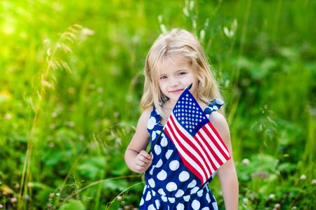 Cute smiling little girl with long curly blond hair holding an american flag on sunny day in summer park. Independence Day, Flag Day concept Stock Photo