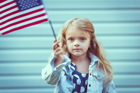 Adorable little girl with long curly blond hair holding american flag and waving it. Independence Day, Flag Day concept. Vintage and retro colors. Instagram filters