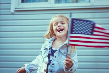 笑いとアメリカの国旗を振って長い巻き毛のブロンドの髪のかわいい女の子。独立記念日、国旗の日コンセプト。ヴィンテージやレトロな色。  写真素材