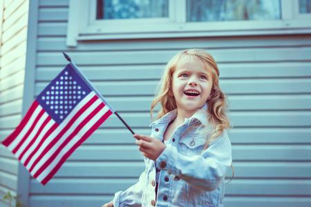 julio: Niña bonita con el pelo largo y rubio y rizado sonriendo y agitando bandera americana. Día de la Independencia, el concepto de Día de la Bandera. Vintage y retro colores. Foto de archivo