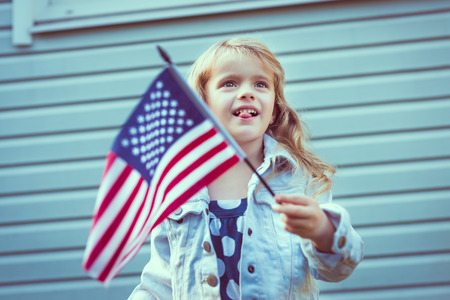 Funny little girl with long curly blond hair putting out her tongue and waving american flag. Independence Day, Flag Day concept. Vintage and retro colors.