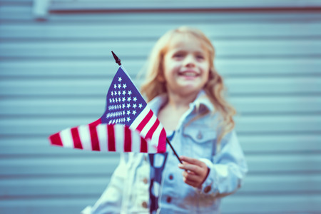 Flying american flag in little girl's hand. Selective focus, blurred background. Independence Day, Flag Day concept. Vintage and retro colors. Instagram filters Stok Fotoğraf