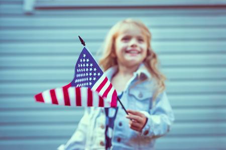 Voando bandeira americana na mão da menina. O foco seletivo, fundo desfocado. Dia da Independência, Dia da Bandeira conceito. Cores do vintage e retro. Filtros Instagram