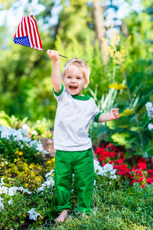 Barefoot little boy with blond hair laughing and waving american flag in sunny park or garden on summer day. Portrait of child on blurred background. Independence Day Flag Day concept Banque d'images