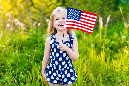おかしいそれを振って、晴れた日に夏の公園で笑っているアメリカのフラグを保持している長い巻き毛のブロンドの髪の少女。独立記念日国旗の日