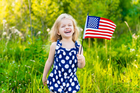 Adorable laughing little girl with long curly blond hair holding american flag and waving it on sunny day in summer park. Independence Day Flag Day concept