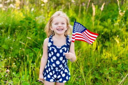ragazze bionde: Bella bambina con lunghi capelli biondi ricci con la bandiera americana in mano che ride sulla giornata di sole nel parco di estate. Concetto Flag Day Independence Day