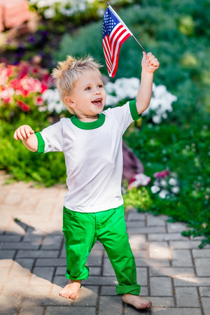 Funny laughing little boy with blond hair holding american flag and waving it in sunny park or garden on summer day. Portrait of child on blurred background. Independence Day Flag Day concept