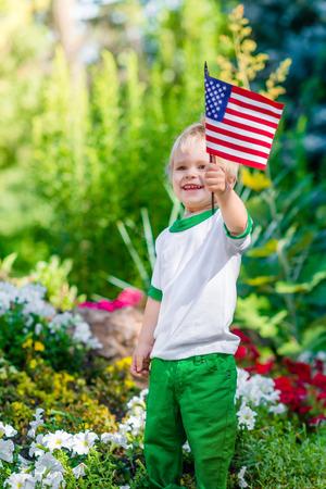 金髪少年アメリカの国旗を保持していると、夏の日の日当たりの良い公園や庭でそれを振ってにこにこしています。背景をぼかした写真の子供の肖