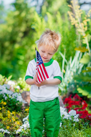 Smiling little boy with blond hair holding american flag and looking at it in sunny park or garden on summer day. Portrait of child on blurred background. Independence Day Flag Day concept Фото со стока