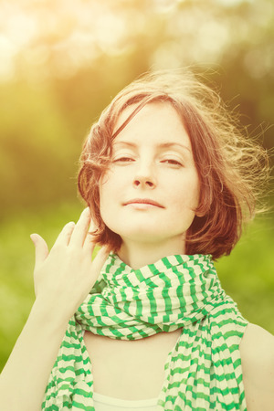 Outdoor portrait of adorable young woman wearing green and white striped scarf with wind in her hair. Summer sunset orange and yellow natural toning Фото со стока