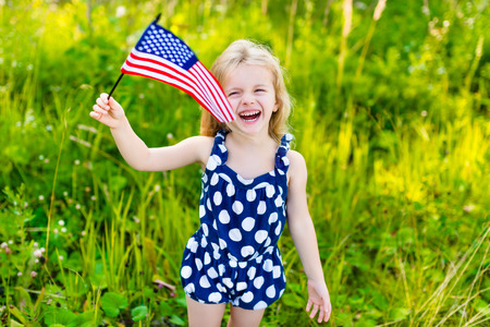 Laughing little girl with long curly blond hair holding american flag and waving it outdoor portrait on sunny day in summer park. Independence Day Flag Day concept