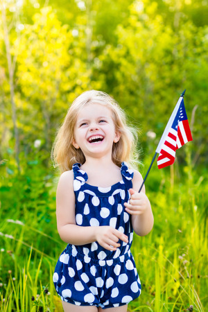Laughing blond little girl with long curly hair holding american flag outdoor portrait on sunny day in summer park. Independence Day Flag Day concept