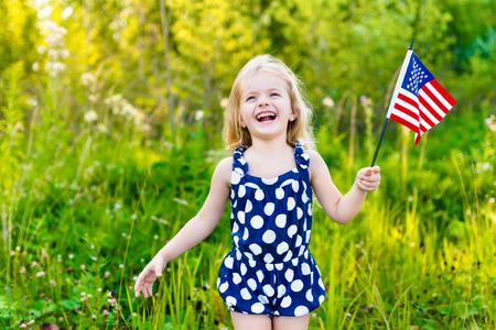 アメリカの国旗を押しそれ夏の公園で晴れた日の屋外のポートレートを振って長い巻き毛の金髪少女を笑っています。独立記念日国旗の日コンセプ