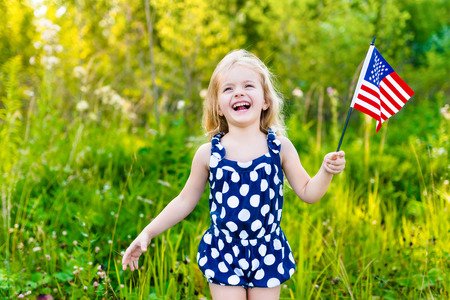 Laughing blond little girl with long curly hair holding american flag and waving it outdoor portrait on sunny day in summer park. Independence Day Flag Day concept Stok Fotoğraf