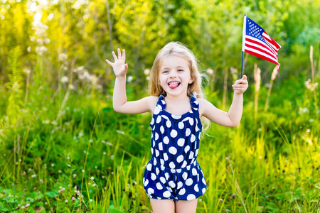 put: Funny little girl with long curly blond hair putting out her tongue and waving american flag outdoor portrait on sunny day in summer park. Independence Day Flag Day concept