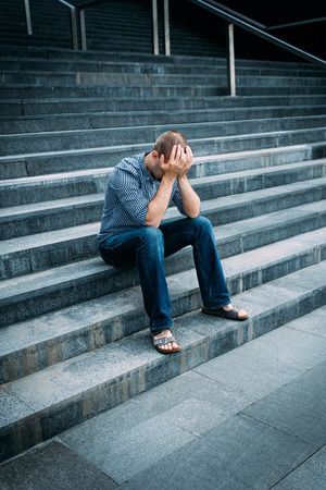 despaired: Despaired young man covering his face with hands sitting on stairs of big building. Feelings of sadness, despair and tragedy