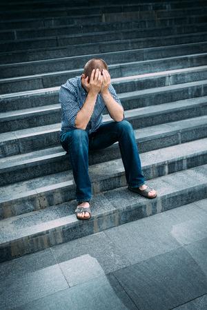 階段の上に座って手で顔を覆う絶望した若い男の屋外のポートレート。悲しみ、絶望と悲劇の気持ち 写真素材