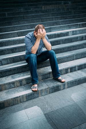 Outdoor portrait of despaired young man covering his face with hands sitting on stairs. Feelings of sadness, despair and tragedy Banque d'images