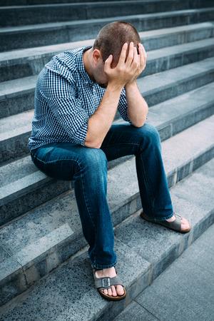 悲しい若い男の大きな建物の階段の上に座って手で顔を覆います。悲しみ、絶望と悲劇の気持ち