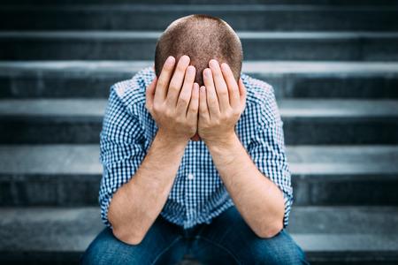 Im Freienportrait des traurigen jungen Mann bedeckte sein Gesicht mit den Händen auf Treppen sitzt. Selektiven Fokus auf den Händen. Traurigkeit, Verzweiflung, Tragödie Konzept
