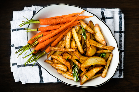 Roasted vegetables seasoned with rosemary and black pepper. Oven-baked baby carrots and potatoes in white bowl on dark table. Healthy vegetarian snack, delicious vegan food