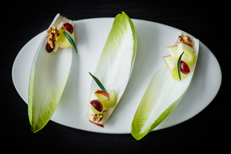Fancy Waldorf salad on endive leaves served in elegant setting. Waldorf salad on white plate on black table, selective focus on details