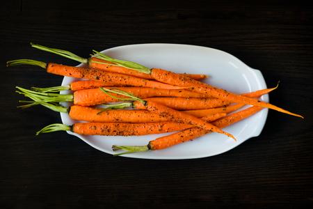 carrot: Zanahorias beb� ovenbaked espolvoreado con pimienta negro freshgrounded en un plato blanco sobre la mesa oscura. Merienda saludable vegetariana deliciosa comida vegana