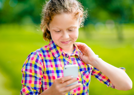 Adorable smiling teenage girl in casual clothes with smartphone in her hand, looking at screen, reading a message   Фото со стока