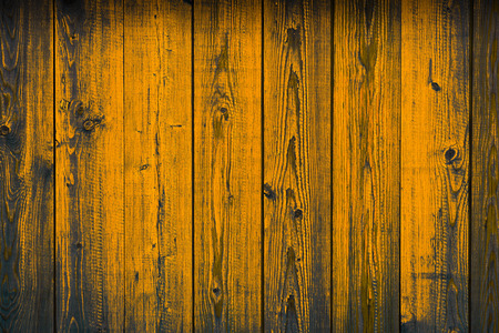 Old wooden yellow painted peeling off planks, texture background