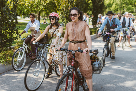 kepi: Toronto, Canada - September 20, 2014: Unidentified participants of Tweed Ride Toronto riding on their bicycles. This annual event also known as Tweed Run is dedicated to the style of old England: people dress up in vintage style clothes and try to reconst Editorial